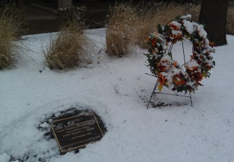 A plaque and wreath in late March 2013 are at the base of a tree planted as a memorial to members of the University of Iowa physics department killed in the Nov. 1, 1991, mass shooting on the UI campus. (Lyle Muller/IowaWatch)