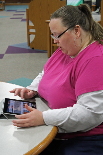 Janet Lubben, North Liberty public library's technology services librarian, downloaded an eBook onto her iPad on April 19. Lubben has been with the library for eleven years and works one-on-one with patrons to help them learn about new technologies in the library.