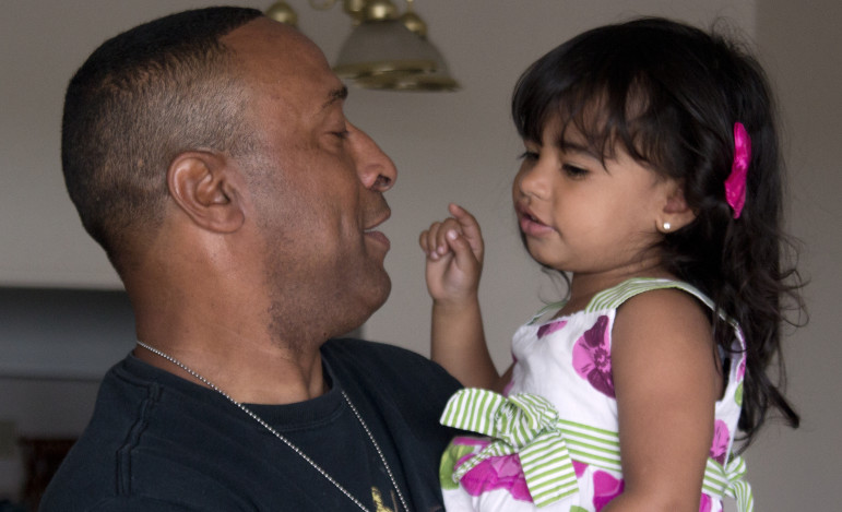 Stephen Leon, a combat veteran who is now 70 percent disabled, holds his granddaughter Ashley A. De Leon at his apartment in Revere, Mass. in June.