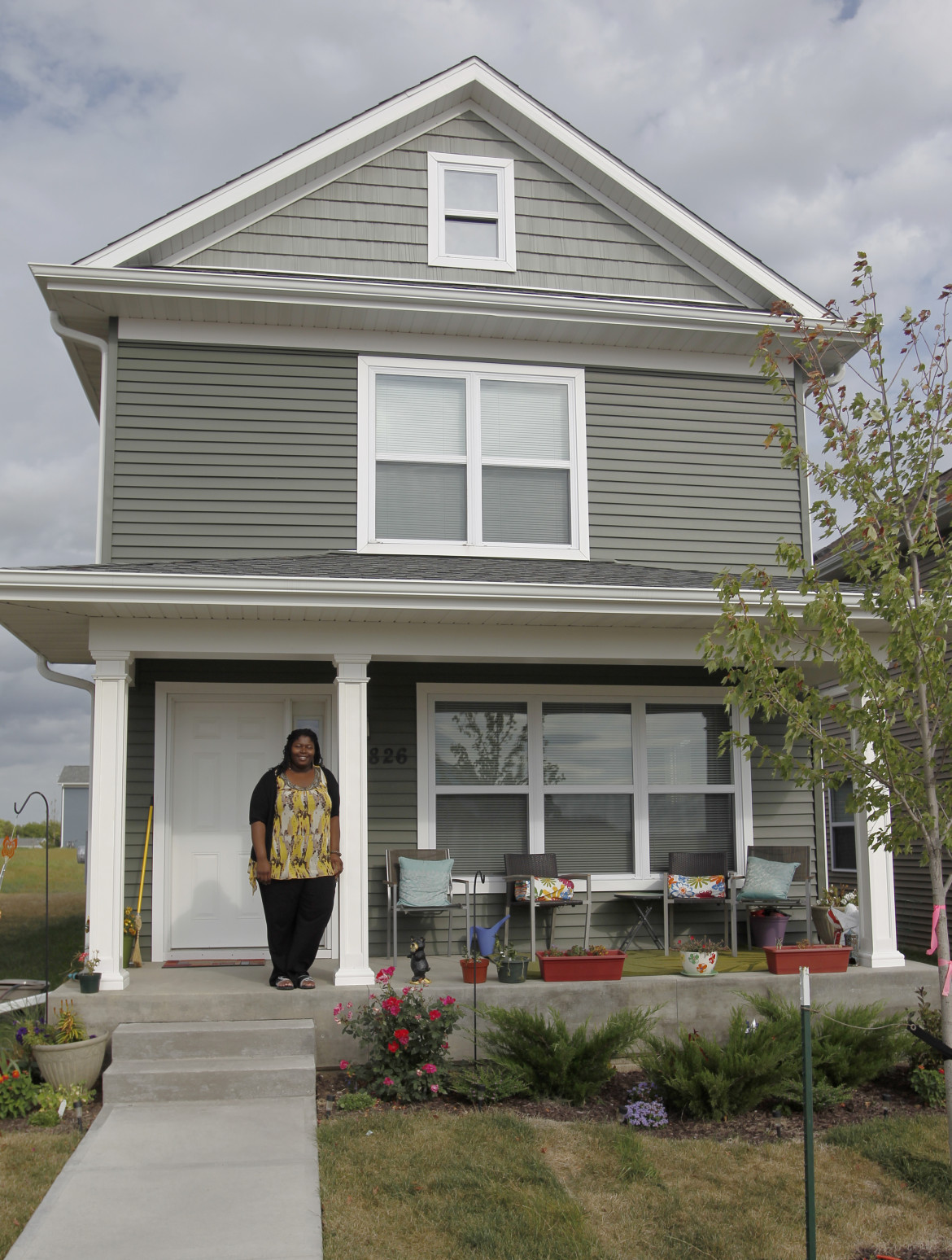 LaTasha Massey stands on the porch of her home on Wednesday, September, 11, 2013 in Iowa City, Iowa. Massey moved in to the house last December participating in a city-run, state-funded program providing down payment assistance to potential home buyers who meet income guidelines.
