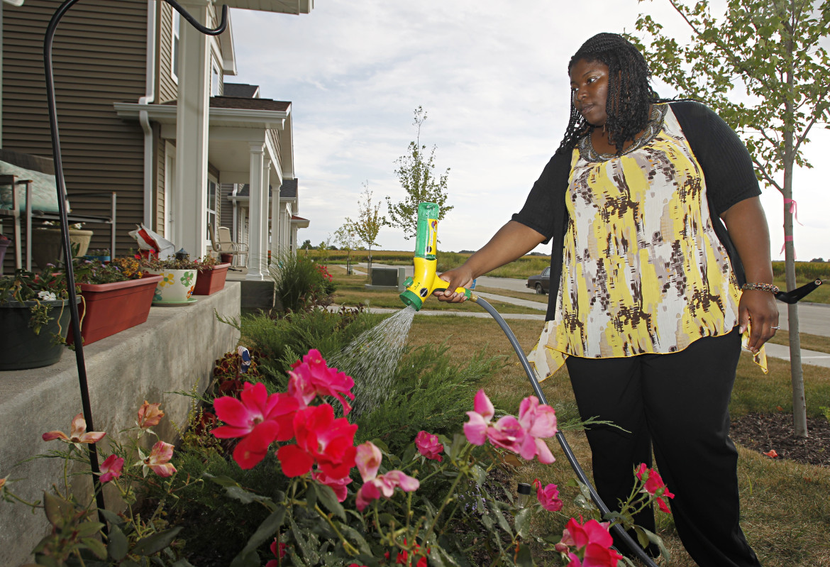 LaTasha Massey waters flowers in her front yard on Wednesday, September, 11, 2013 in Iowa City, Iowa. Massey moved in to the house last December participating in a city-run, state-funded program providing down payment assistance to potential home buyers who meet income guidelines.