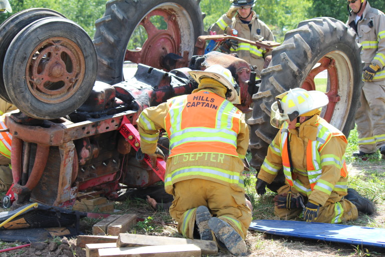 Eastern Iowa firefighters practice their response to a farmer pinned beneath a rolled over tractor in Tractor Rollover Extrication Training, by the Rural Health and Safety Clinic of Greater Johnson County, on Aug. 3 at the Johnson County Extension Building in Iowa City.