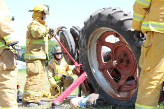Eastern Iowa firefighters practice their response to a farmer pinned beneath a tractor during a Tractor Rollover Extrication Training, by  the Rural Health and Safety Clinic of Greater Johnson County on Aug. 3, 2013, at the Johnson County Extension Building in Iowa City.