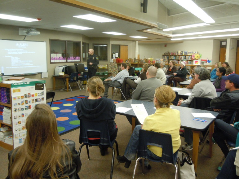 Parents listen while Iowa City Police Officer Derek Frank presents information on ALICE during an informational meeting.