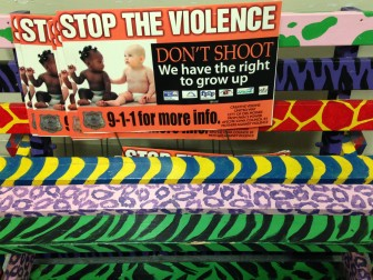 Signs and a bench at Creative Visions promote the organization' s message against violence in northwest Des Moines.