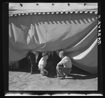 Boys sneaking under a circus tent in Roswell, New Mexico in 1936.