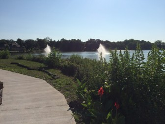 A view of two water fountains in Meyers Lake, from Angels' Park Memorial Island in Evansdale.