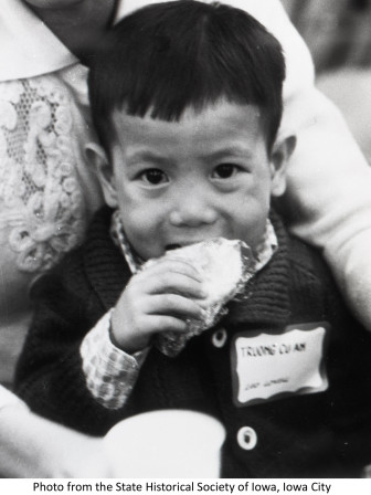 A Vietnamese boy eating a cracker in Des Moines in 1975.