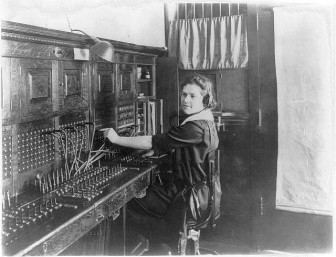 Young woman seated at switchboard circa 1922.