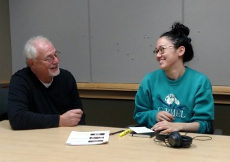 IowaWatch Executive Director-Editor Lyle Muller tells photographer Danielle Wilde (right) on Nov. 13, 2015, that she has won the IowaWatch/Fotini Perlmutter Award for outstanding work with the nonprofit news organization.