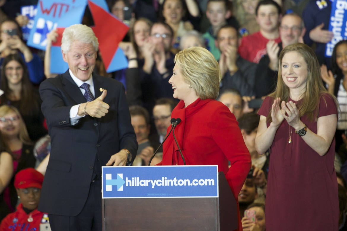 Husband and former President Bill Clinton gives wife and current presidential candidate Hillary Clinton a thumbs-up as she addresses a crowd of her supporters at Drake University in Des Moines, Iowa, after the Feb. 1, 2016, Iowa precinct caucuses. The couple's daughter, Chelsea Clinton, also was at the post-caucus rally.