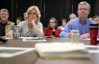 Kathy Kachel (center), a Wisconsin homeowner whose house overlooks Pattison SandÕs Iowa operations, reacts to testimony given by professor Patrick O'Shaughnessy at a meeting of the Mine Reserve Expansion Study Committee. In the foreground are commitee members Anne Osmundson and Tom Blake.