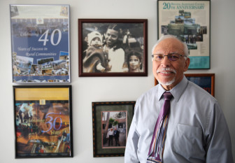 WASHINGTON, DC - JUNE 18: Moises Loza, executive director of the Housing Assistance Council, in his office in Washington, D.C. An old photograph of his family hangs among posters commemorating the council's work over the years.