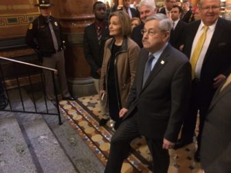 Iowa state Sen. Liz Mathis, D-Robins, helps escort Gov. Terry Branstad into the Iowa House chamber for Branstad's annual Condition of the State address on Jan. 10, 2017.